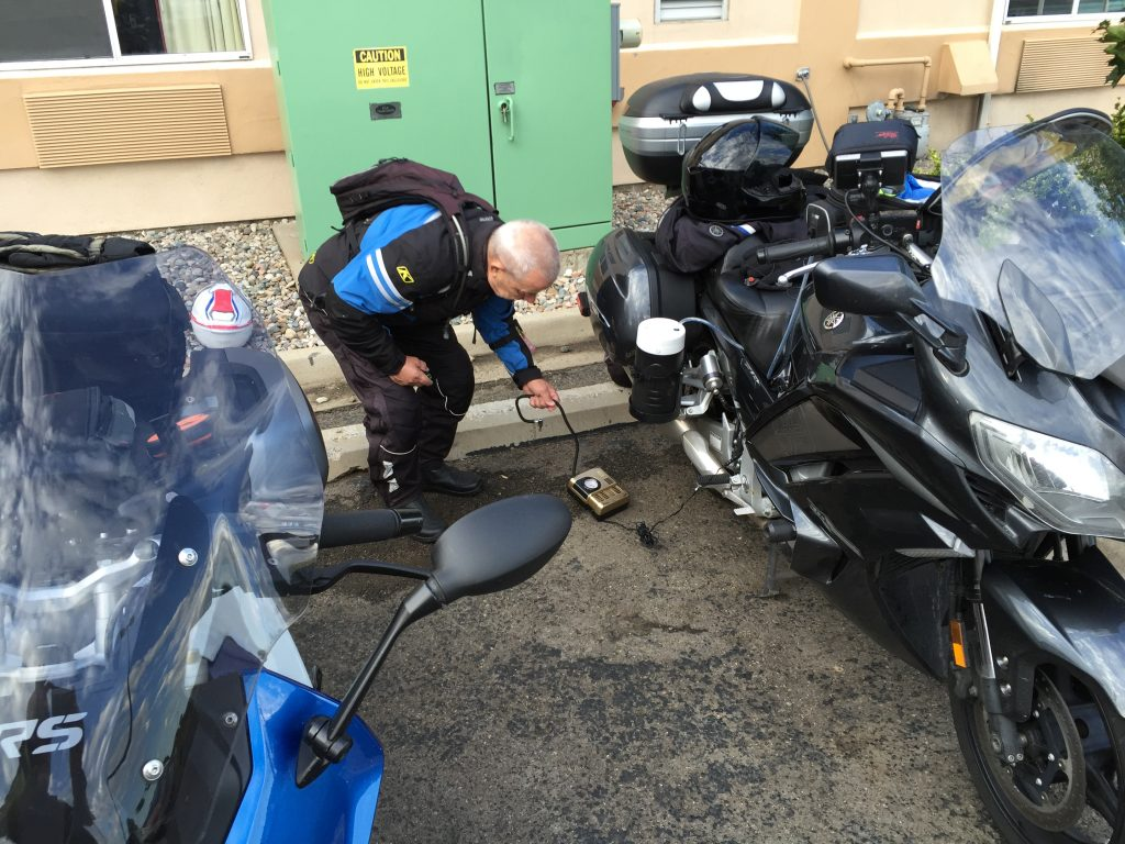 Petey borrowing Bob's air pump to check his bike's tire pressures.